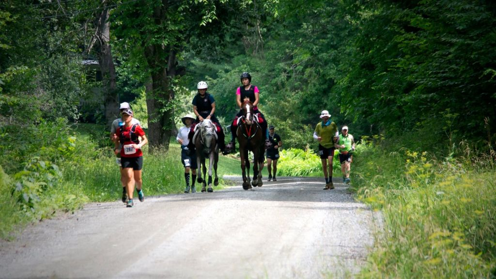 2020-vermont-100-endurance-riders-nancy-and-charlotte-zukewich-dirt-raod-with-runners.jpeg