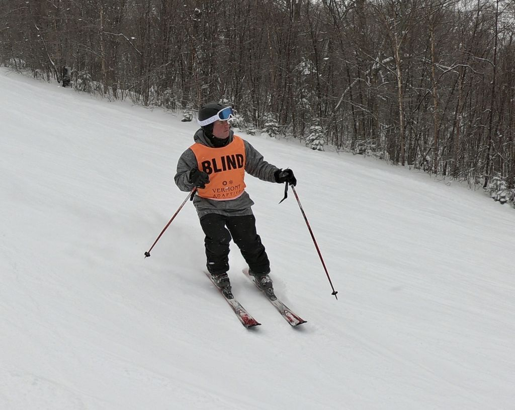 A blind skier faces down slope while carving a turn at the USABA / Vermont Adaptive 13th Annual Ski Festival Weekend in Vermont
