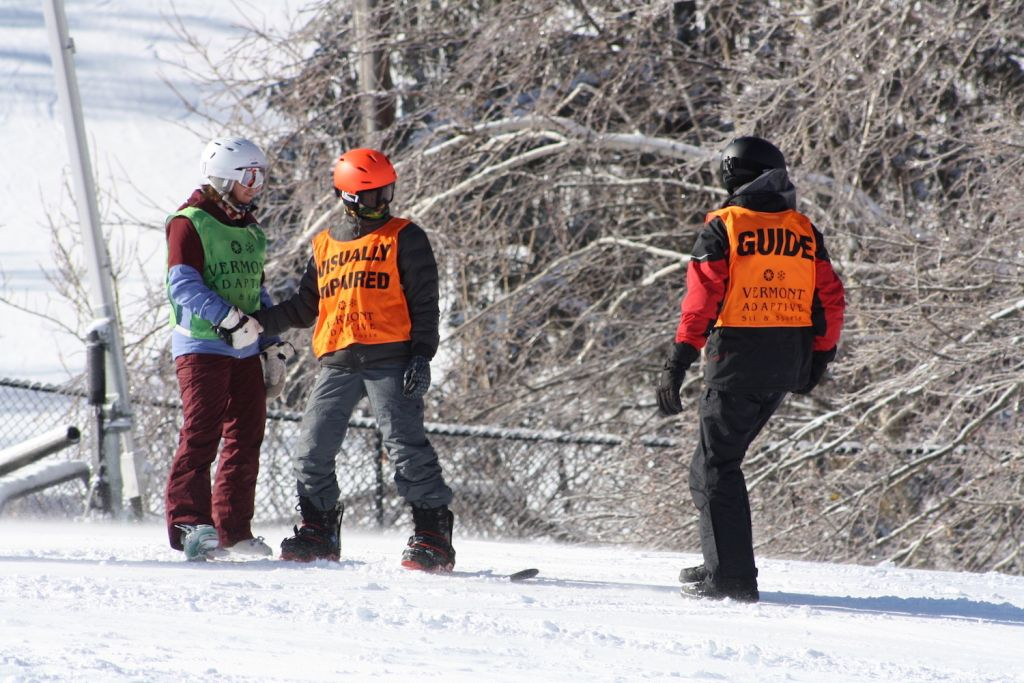 A visually impaired snowboarder works with two Vermont Adaptive guides at the 13th Annual USABA / Vermont Adaptive Ski Festival Weekend