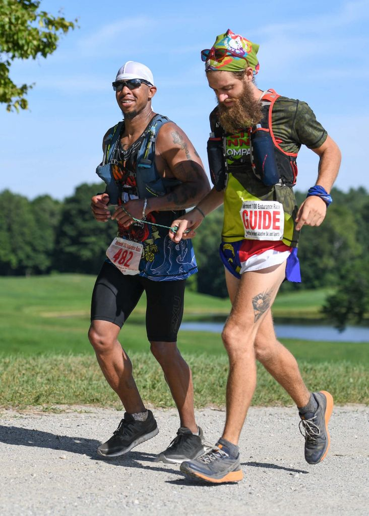 A visual impaired athlete and their guide race along the Vermont 100 with open fields around them.
